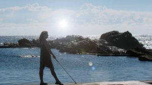 Woman walking by a pool with cane